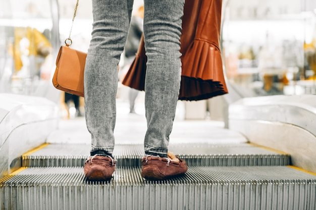 Pernas de pé na escada rolante de um shopping
