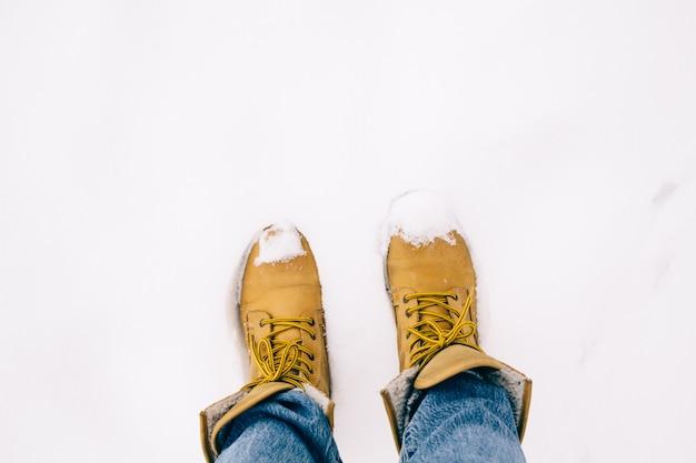Pernas de pessoa em botas amarelas com jeans azul na neve, o inverno está chegando