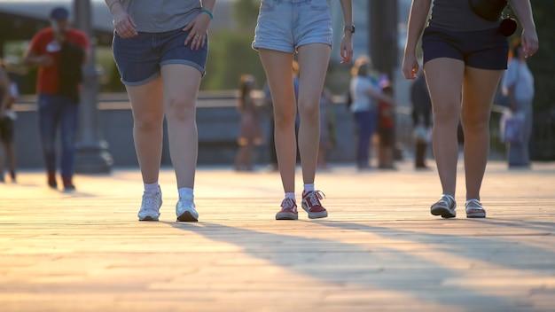 Pernas de pessoas caminhando ao pôr do sol. lazer e recreação na cidade