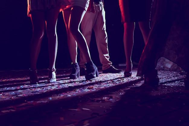 Pernas de pessoas dançando na festa.