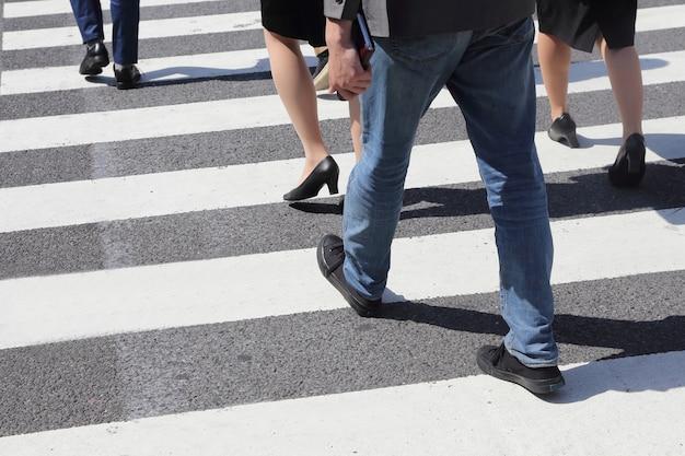Pernas de pessoas não identificadas, atravessando a rua