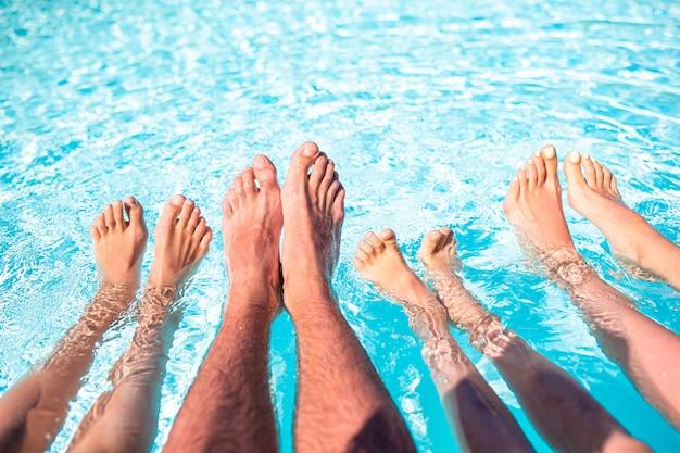 Pernas de quatro pessoas ao lado da piscina