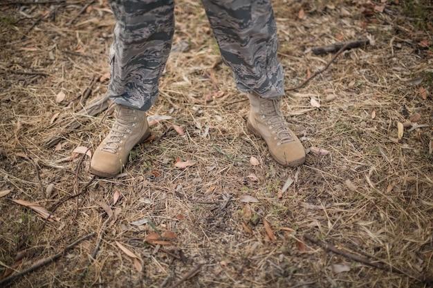 Pernas de soldado militar em pé no campo de treinamento