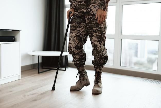Pernas de soldados closeup apoiando-se na muleta perto do sofá