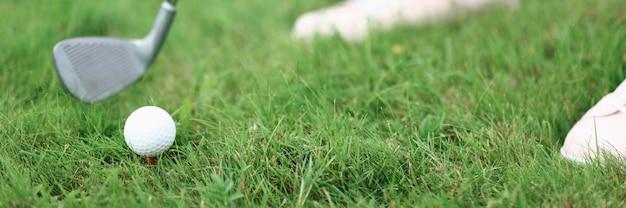 Pernas de tacador de ferro e bola na grama