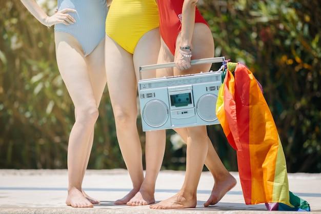 Pernas de três mulheres carregando um rádio-toca-fitas com uma bandeira lgtb
