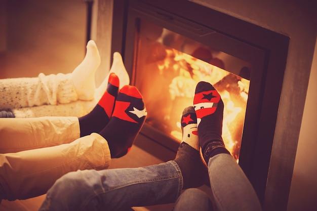 Pernas de um grupo de amigos relaxando na lareira