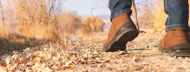 Pernas de um homem caminhando ao ar livre. natureza da temporada do outono do estilo da moda do estilo de vida no fundo.