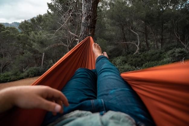 Pernas de um homem de jeans esticadas dentro de uma rede pendurada entre as árvores da floresta