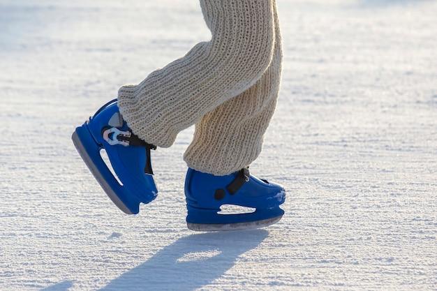 Pernas de um homem de patins azuis andando em uma pista de gelo