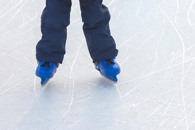 Pernas de um homem de patins azuis andando na pista de gelo