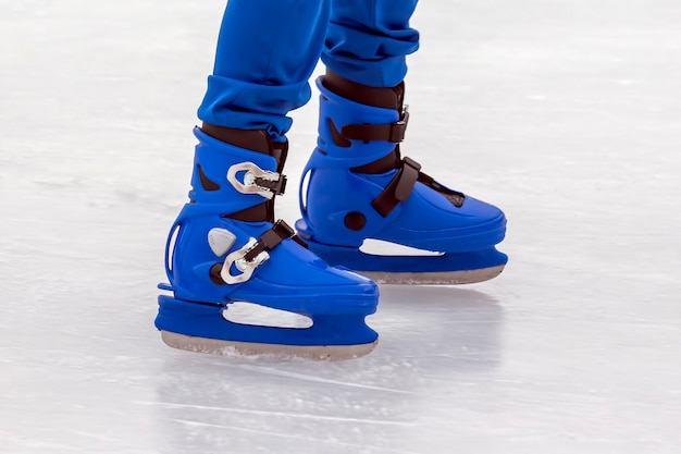 Pernas de um homem de patins azuis em uma pista de gelo. hobbies e esportes. férias e atividades de inverno.