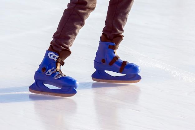 Pernas de um homem de patins azuis em uma pista de gelo. passatempos e lazer. esportes de inverno