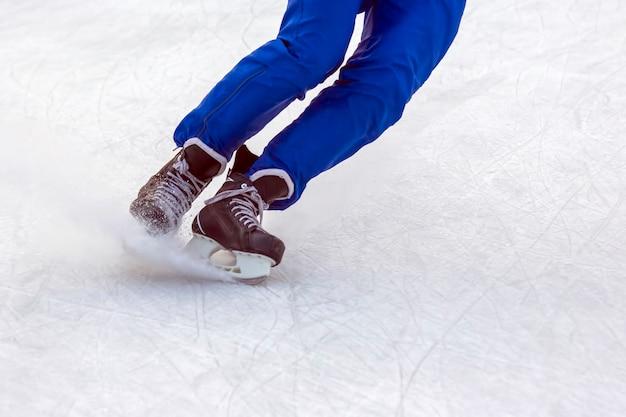 Pernas de um homem de patins de gelo patinam ativamente em uma pista de gelo no inverno. hobbies e esportes.