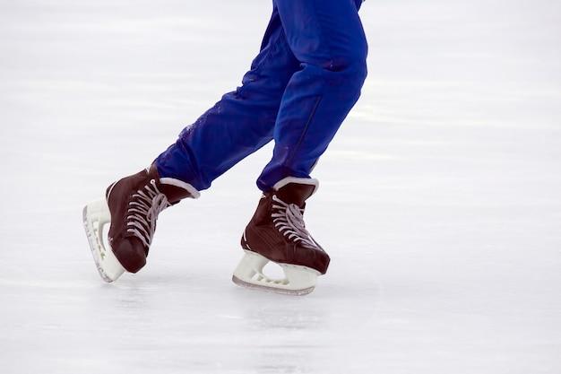 Pernas de um homem patinando em uma pista de gelo. hobbies e esportes. férias e atividades de inverno.