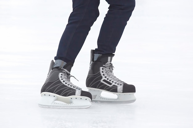 Pernas de um homem patinando em uma pista de gelo