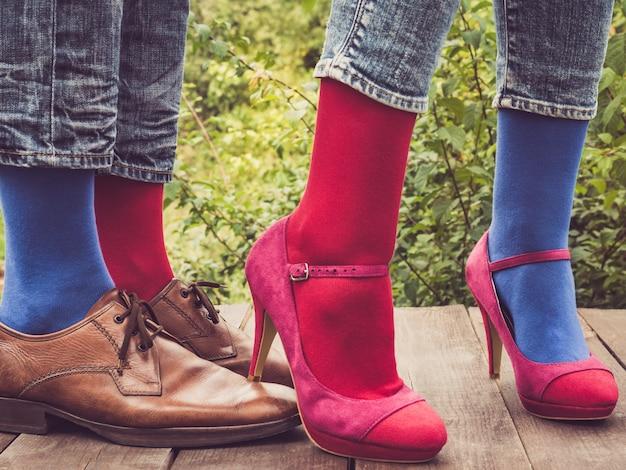 Pernas de um jovem casal em sapatos elegantes e meias coloridas