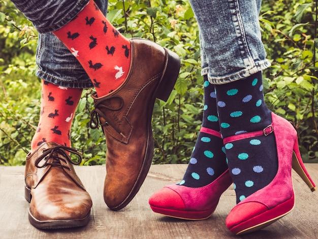 Pernas de um jovem casal em sapatos elegantes, meias brilhantes, coloridas