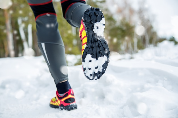 Pernas de um jovem corredor fora na natureza de inverno