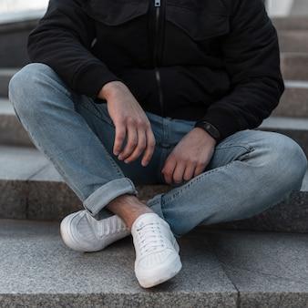 Pernas de um jovem em jeans e tênis elegantes de couro branco