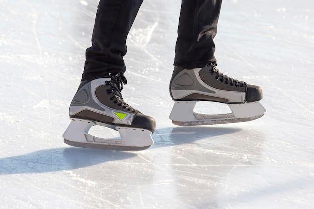 Pernas de um patinador na patinação no gelo na pista de gelo de rua. esporte de inverno. passatempos e recreação ativa nos esportes.
