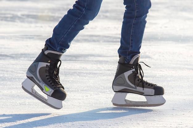 Pernas de um patinador na patinação no gelo na pista de gelo de rua. esporte de inverno