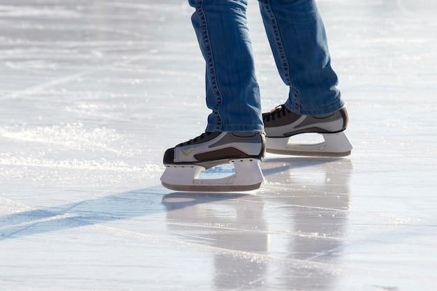 Pernas de um patinador na patinação no gelo na pista de gelo de rua.