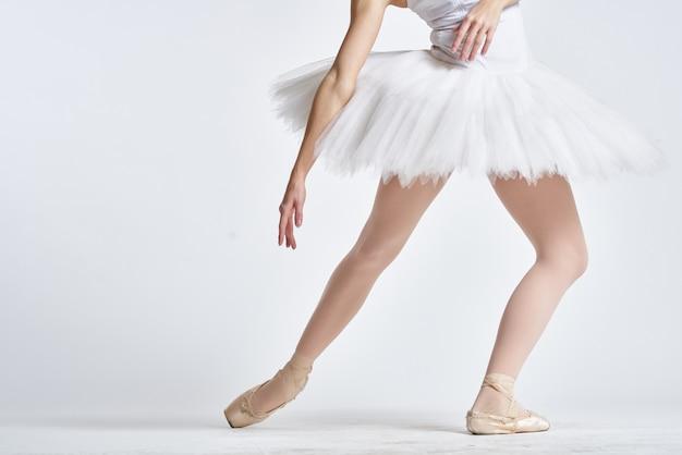Pernas de uma bailarina em sapatilhas em uma parede de luz