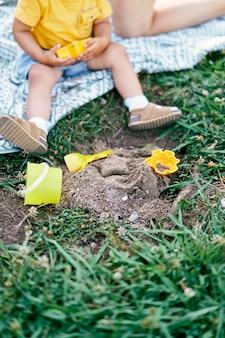 Pernas de uma criança sentada em um cobertor em um gramado verde ao lado de brinquedos