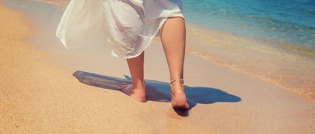 Pernas de uma garota à beira-mar.