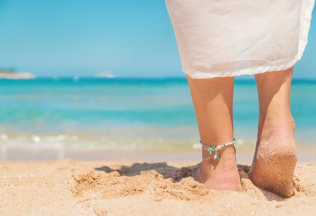 Pernas de uma garota à beira-mar