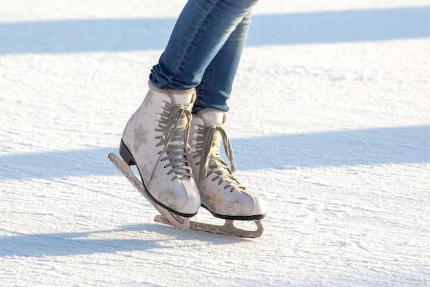 Pernas de uma garota de jeans e patins brancos em uma pista de gelo. passatempos e lazer. esportes de inverno