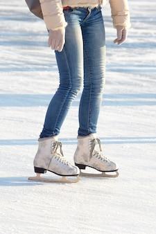 Pernas de uma garota de jeans e patins brancos em uma pista de gelo