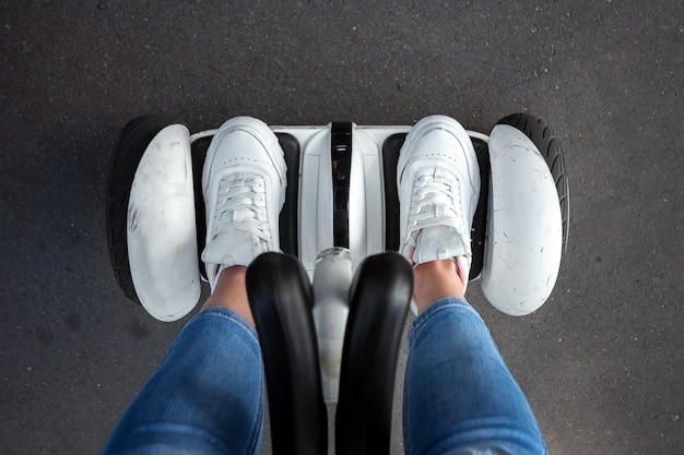 Pernas de uma garota de tênis branco em um hoverboard branco em um close-up do parque