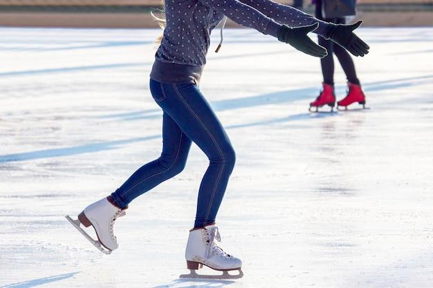 Pernas de uma garota em jeans azul e patins brancos na pista de gelo.
