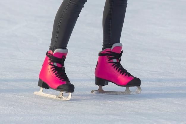 Pernas de uma garota patinando no gelo em uma pista de gelo. hobbies e esportes. férias e atividades de inverno