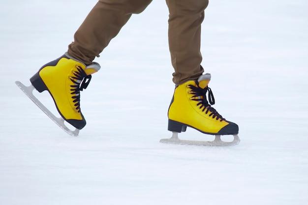 Pernas de uma garota patinando no gelo em uma pista de gelo. hobbies e esportes.