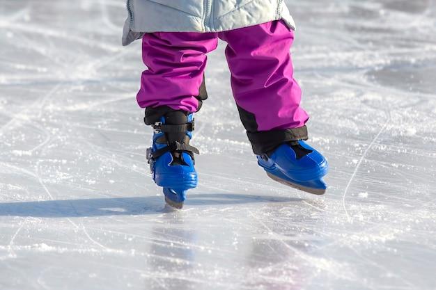 Pernas de uma garota patinando no gelo em uma pista de gelo. passatempos e lazer. esportes de inverno