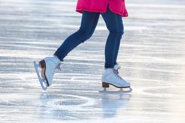 Pernas de uma garota patinando no gelo em uma pista de gelo
