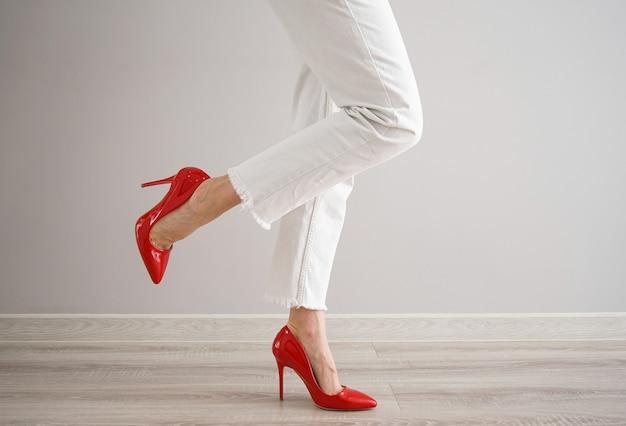 Pernas de uma jovem em jeans brancos e sapatos vermelhos em fundo cinza.