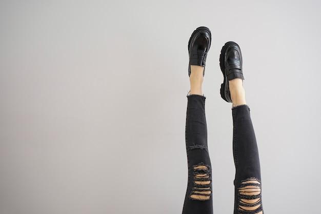Pernas de uma jovem em jeans e sapatos em fundo cinza, lugar para texto.