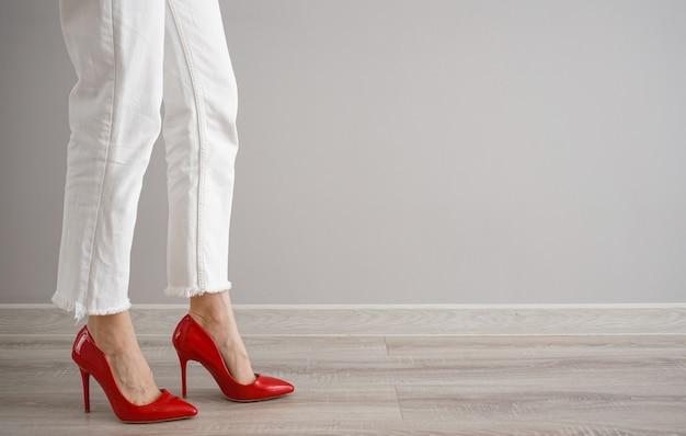 Pernas de uma jovem em jeans e sapatos em um fundo cinza, espaço para texto.