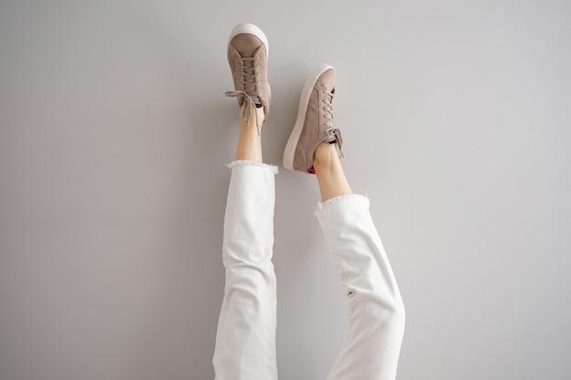 Pernas de uma jovem garota em jeans e tênis em fundo cinza.