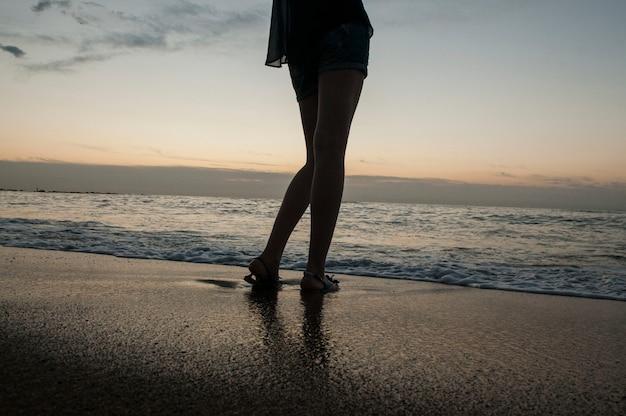 Pernas de uma jovem no mar e praia arenosa
