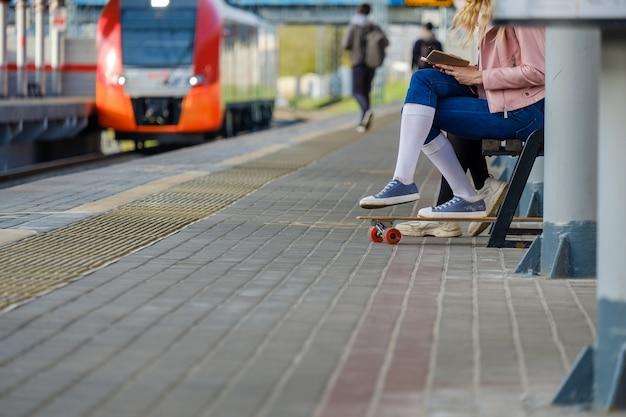 Pernas de uma menina de meias brancas e tênis, encostada em um skate.