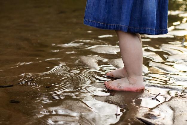 Pernas de uma menina em um vestido jeans em pé na areia da margem de um rio na água no verão. infância.