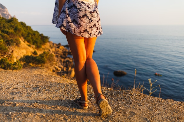 Pernas de uma menina em um vestido na praia ao pôr do sol