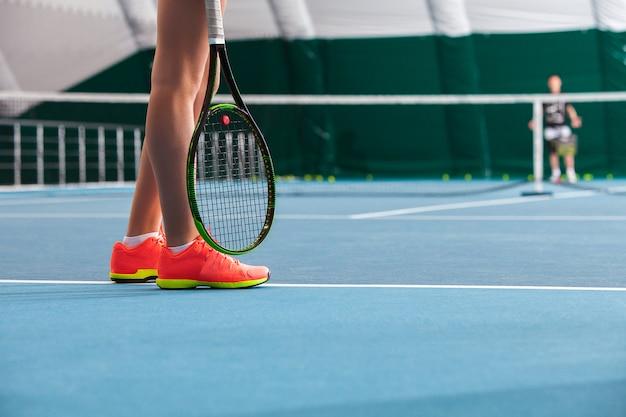 Pernas de uma menina em uma quadra de tênis fechada com bola e raquete