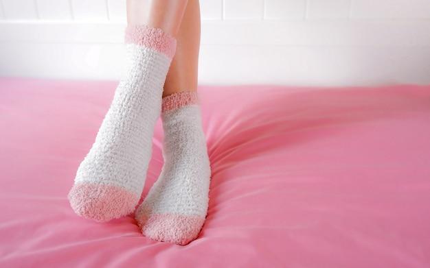 Pernas de uma mulher bonita estão vestindo meias quentes no quarto. meias de moda rosa.
