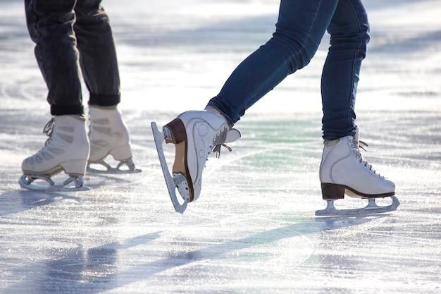 Pernas de uma mulher de jeans e patins brancos em uma pista de gelo. passatempos e lazer. esportes de inverno